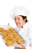 Chef Bakes Cookies. Pretty, mature female chef in her uniform, inhaling the aroma of a tray of her fresh baked chocolate chip cookies.  Isolated on white Royalty Free Stock Photography