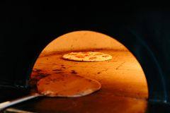 Chef Baking Caprese Bianca Pizza inside wood burning pizza oven. Ingredients are Mozzarella, Parmesan, Olive oil, sliced tomato. Chef Baking Caprese Bianca stock images