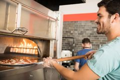 Chef Baking Pizza Bread In Oven At Commercial Kitchen Royalty Free Stock Photo