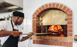 Chef baking pizza in wood fired oven. Chef baking pizza in the wood fired oven at commercial kitchen. Cook baking pizza in a traditional stone oven at restaurant stock photo