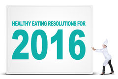 Chef and banner of healthy eating resolutions. Young female chef wearing uniform and pushes a big board with a text of healthy eating resolutions for 2016 Royalty Free Stock Photos