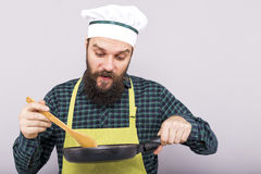 Chef with beard tasting the food with a wooden spoon Stock Photo