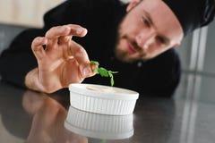 chef beau ajoutant le persil au plat Image stock