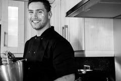 Chef beau souriant comme il se tient dans la cuisine se préparant à la cuisson photo stock