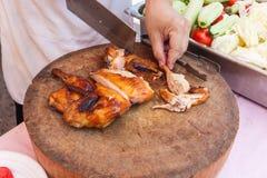 Chef benutzen das Küchenmesserhuhn, das auf hölzernem Block gegrillt wird Stockfotos