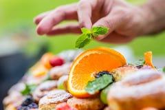 Chef bereitet eine Platte von Kuchen mit frischen Früchten vor Er arbeitet an der Krautdekoration Gartenfest im Freien stockfotografie