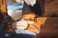 Chef bereitet einen saftigen Hamburger an Bord zu Stockfotografie