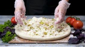 Chef bespr?ht Pizza mit geriebenem K?se Feld Berufspizzeriachef in den Handschuhen setzt letzte Schicht K?se auf Schwarzes stock footage
