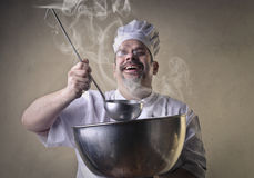 Chef with big pot. Chef with a joyful face smelling the scent coming out of a big pot with a big spoon Royalty Free Stock Image