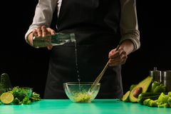 Chef on a black background makes juice from vegetables with water for the preparation of a green detox smoothie. Healthy, clean stock photos