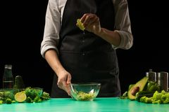 Chef on a black background pouring lime juice on vegetables for cooking cooking green detoxification smoothies. Healthy, clean. Food, weight loss food concept royalty free stock images