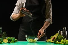 Chef on a black background salting vegetables for cooking green detox smoothies. Healthy, clean food, weight loss concept, sport royalty free stock photos