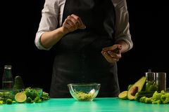 Chef on a black background salting vegetables for cooking green detox smoothies. Healthy, clean food, weight loss concept, sport stock images