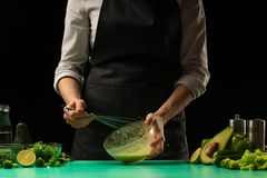 Chef on black background whips juice from vegetables for cooking green detoxification smoothies. Healthy, clean food, weight loss. Food concept, sport royalty free stock image