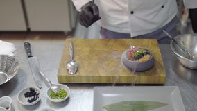 Chef in black rubber gloves finishing to prepare dish with raw tuna and salmon in modern restaurant kitchen close-up. Male putting the bowl with food on stock video