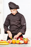 Chef in black uniform cutting fruit Royalty Free Stock Images