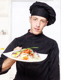 Chef in black uniform offer salad Royalty Free Stock Images
