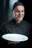 Chef in black uniform showing a plate Stock Photography