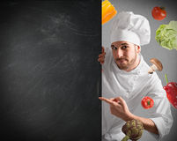 Chef with blackboard. Smiling chef with blackboard and vegetables background Royalty Free Stock Photography