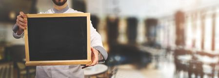 Chef with blank blackboard standing in restaurant. banner royalty free stock photos