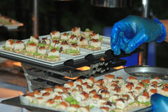 Chef in blue catering gloves arranging canapés Royalty Free Stock Images