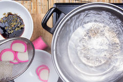 Chef boiling kamaboko fish cake in pot Stock Image