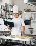 Chef With Book Standing By Kitchen Counter Royalty Free Stock Photos