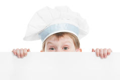 Chef boy with blank billboard. Child chef in white uniform and hat hiding behind empty board isolated stock image