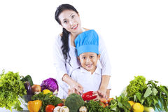 Chef boy with mom on white. Chef boy is learning how to cut vegetable on white background royalty free stock photos