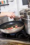 Chef or braising meat in a frying pan Stock Photo