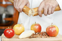 Chef Breaks Baguette, Close. Close-up of a chef breaking a baguette over a cutting board of apples, pecans, a tomato and brie Royalty Free Stock Photo