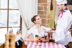 Chef brings a dish pretty woman in a restaurant Royalty Free Stock Photography