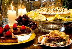 Chef Bubbies Desert Combo. Chocolate Raspberry Torte, Lemon Meringue Pie, and Pecan Pie all surrounded by warm candlelit Kitchen Stock Photos