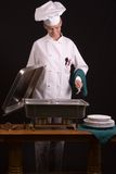 Chef at buffet. Passive posed uniformed female Chef viewing at sideboard holding a spoon Stock Images