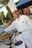 Chef at buffet. Chef showing food on chafing dish at buffet outdoor Stock Image
