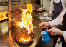 Chef is burning aromatic herbs to smoke a dish Royalty Free Stock Photo