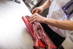 Chef or butcher dicing meat. Chef or butcher dicing lean red meat with a sharp knife on a chopping board in a commercial kitchen while preparing a dinner or cuts stock image