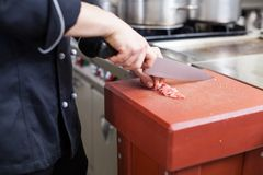 Chef or butcher dicing meat Royalty Free Stock Photos
