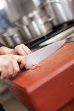 Chef or butcher dicing meat. Chef or butcher dicing lean red meat with a sharp knife on a chopping board in a commercial kitchen while preparing a dinner or cuts stock photography