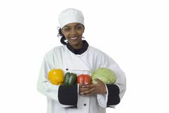 Chef, cabbage and peppers. Studio isolated woman female chef with green cabbage, red and yellow peppers on white Royalty Free Stock Photography