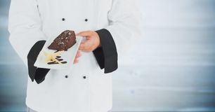 Chef with cake against blurry grey wood panel Royalty Free Stock Photo