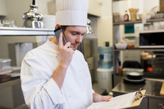 Chef calling on smartphone at restaurant kitchen royalty free stock photography