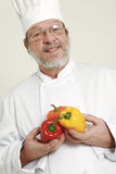 Chef and capsicum. Smiling senior chef having colorful capsicum in hands royalty free stock photo
