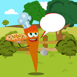 Chef carrot with pizza showing thumb up on a meadow with speech bubble Royalty Free Stock Images