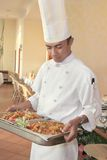 Chef carrying food for buffet. Chef carrying food on chafing dish for buffet Royalty Free Stock Photos
