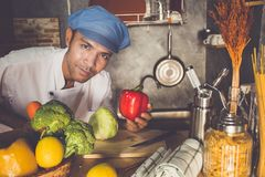 Chef checking. A man of  chef In his kitchen checking vegetable and food for his menu Royalty Free Stock Photography
