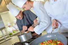 Chef checking trainee`s pan food stock images