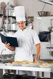 Chef With Checklist And Pasta Dishes At Counter. Young male chef with checklist and variety of pasta dishes at commercial kitchen counter Stock Photography