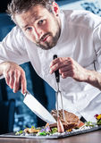Chef. Chef with knife and fork. Professional chef in a restaurant or hotel prepares or cut up t-bone steak. Chef preparing steak. royalty free stock image