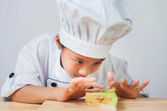 Chef child,Girls wear chef costumes. She is cooking intently Royalty Free Stock Photography